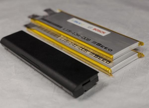 Neue Batterie aus Festkörperzellen verglichen mit einer Netbook-Batterie. Bosch verfügt durch den Zukauf von Seeo Inc. nun über erste Musterzellen, die das Potenzial besitzen, den hohen Anforderungen der Automobilindustrie an Dauerhaltbarkeit und Sicherheit gewachsen zu sein. Der Weltkonzern sieht das Potenzial, mit den neuen Festkörperzellen die Energiedichte bis 2020 mehr als zu verdoppeln und die Kosten nochmals deutlich zu senken.